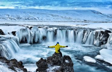 Adventurous man at Godafoss on Iceland_571847170