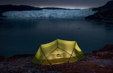 A lamp lit tent near the Eqi Glacier at dusk in Greenland - Mads Pihl - Visit Greenland
